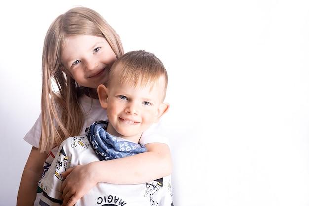 Двое счастливых маленьких детей - сестра и брат улыбаются и обнимаются на светлой белой поверхности