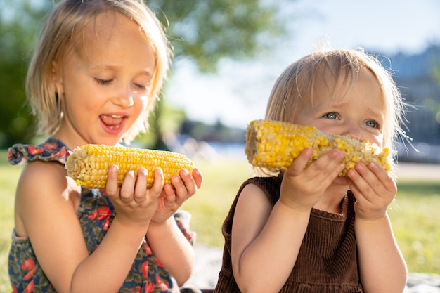 Two happy little childs girls sisters eat sweet corn cob at summer day. healthy eating, picnic