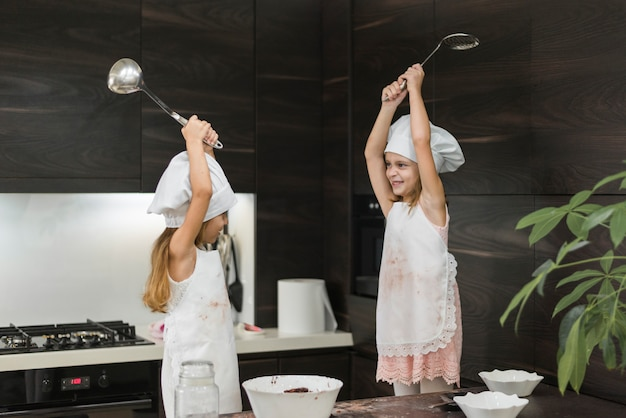 Two happy little girls in chef's hats fighting with kitchen utensil