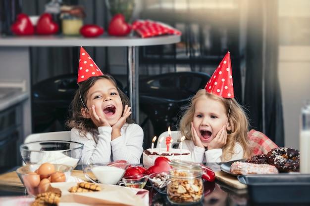 テーブルでケーキと誕生日を祝う2人の幸せな女の子の子供は素敵で美しいです