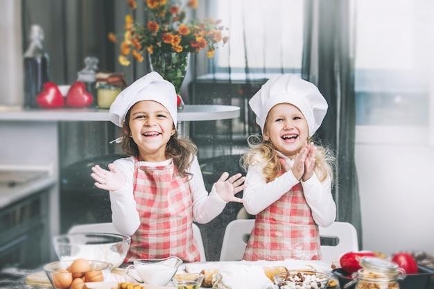 キッチンのテーブルで小麦粉と生地で調理する2人の幸せな小さな女の子の子供は素敵で美しいです