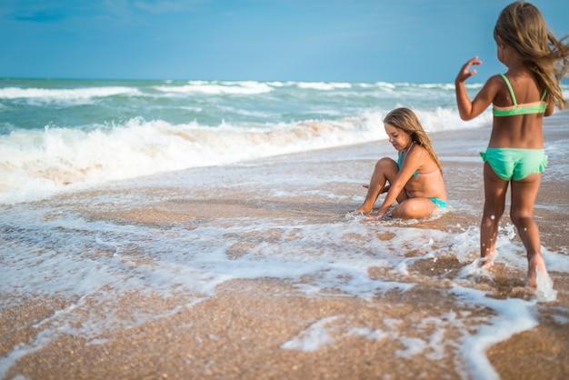 두 행복한 어린 소녀는 모래 해변에서 휴가를 즐기거나 휴가 기간 동안 화창한 여름 날에 바다 파도에 감탄