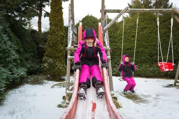 Две счастливые маленькие девочки веселятся на детской площадке в холодный снежный день