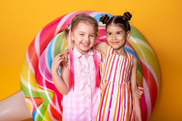 ロリポップと黄色の背景で楽しんで抱き締めて笑っているカラフルなドレスの2人の幸せな少女