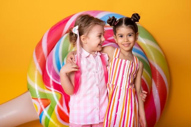 ロリポップと黄色の背景で楽しんで抱き締めて笑っているカラフルなドレスを着た2人の幸せな少女。