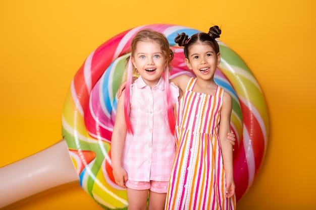 ロリポップと黄色の背景で楽しんで抱き締めて笑っているカラフルなドレスを着た2人の幸せな少女