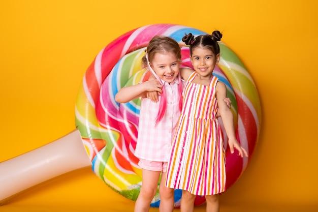 黄色の背景で楽しんで抱き締めて笑っているカラフルなドレスを着た2人の幸せな少女