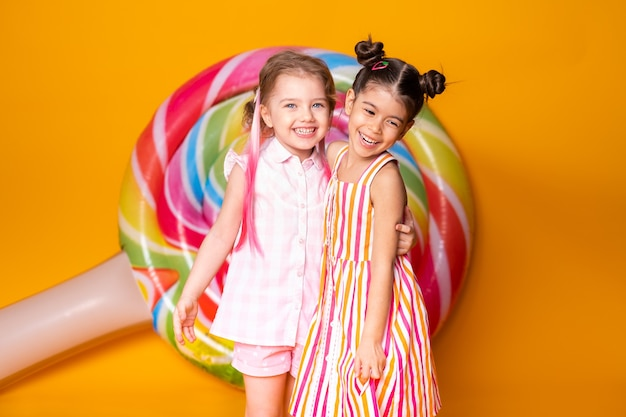 ロリポップを楽しんで抱き締めて笑っているカラフルなドレスを着た2人の幸せな少女。