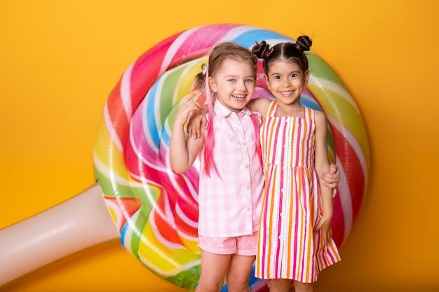 カラフルなドレスを着た2人の幸せな少女が楽しんで抱き締めて笑っています。