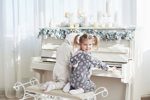 Two happy little girls in pajamas play the piano on christmas day