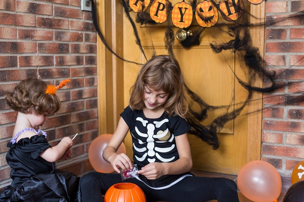Two happy little sisters having fun at home wearing halloween costumes and playing with pumpkins. trick or treat. indoors. lifestyle
