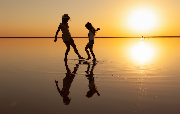 Two happy lovely sisters are walking along the mirror salt lake enjoying the evening fiery sunset