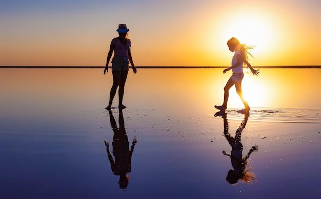 두 행복한 사랑스러운 자매가 저녁 불타오르는 일몰을 즐기며 거울 소금 호수를 따라 걷고 있다