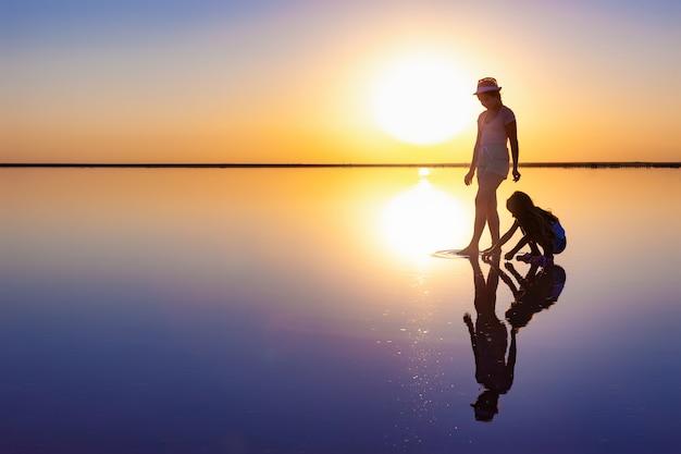 두 행복한 사랑스러운 자매가 저녁 불 같은 일몰을 즐기고 거울 소금 호수를 따라 걷고 있습니다