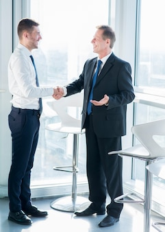 Two happy male business partners shaking hands in office