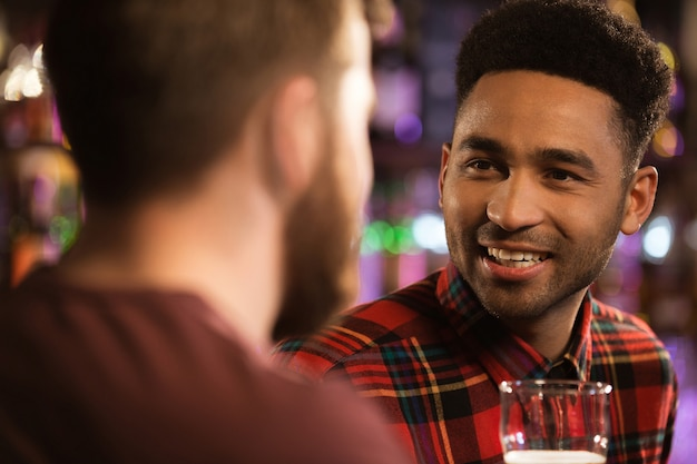 Two happy male friends drinking beer at bar