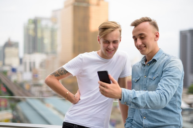 Two happy man using mobile phone outdoors