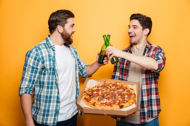 Two happy men drinking beer and eating pizza while looking to each other over yellow wall