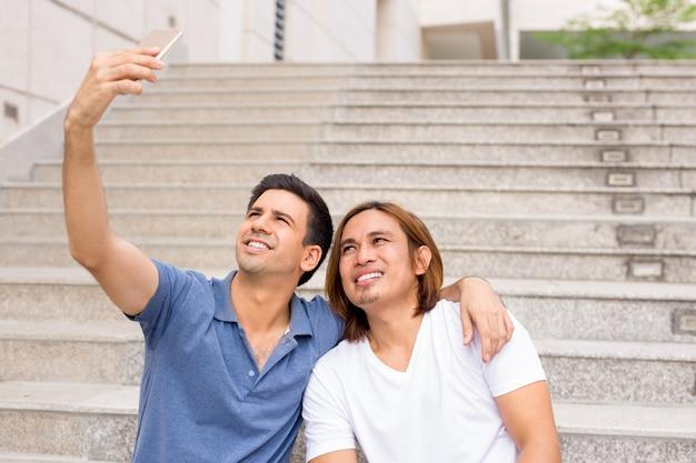 야외 계단에 selfie를 복용 두 행복 한 남자