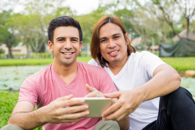 공원에서 스마트 폰을 사용 하여 두 명의 행복 한 남자