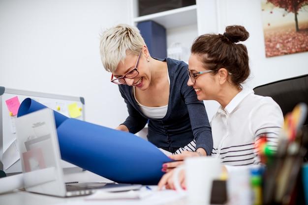 Две счастливые мотивированные улыбающиеся бизнес-леди работают вместе над планированием нового проекта в офисе.