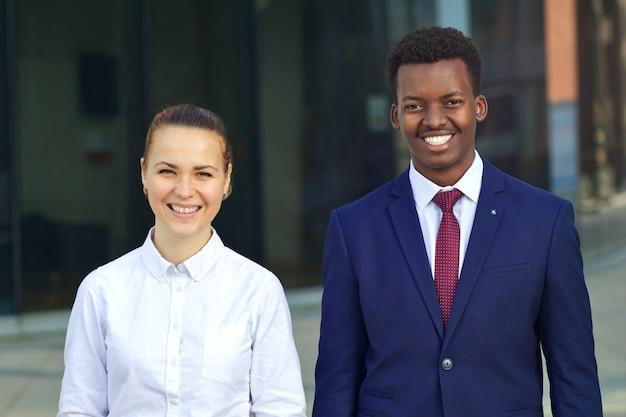 Улыбка двух счастливых многонациональных молодых студентов или рабочих. черный африканский афро-американский бизнесмен и белая женщина работают вместе.
