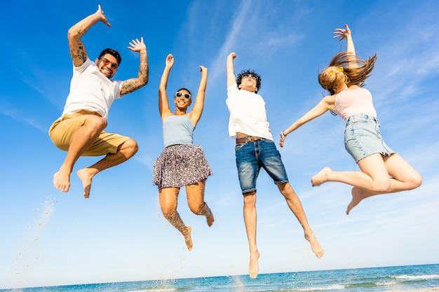 두 명의 행복한 다인종 커플이 휴가 중에 웃고 있는 하늘을 향해 팔짱을 끼고 바닷물 위에서 함께 점프한다