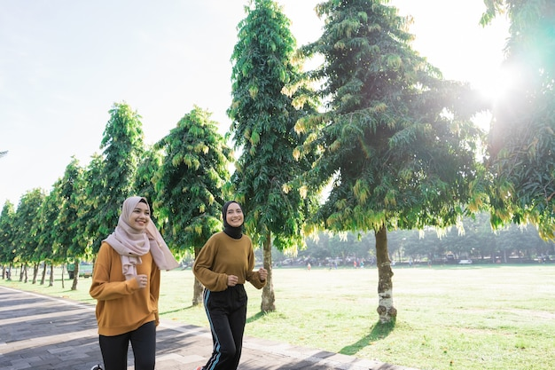 Two happy muslim girls in headscarves do outdoor sports while jogging together in the park with copyspace