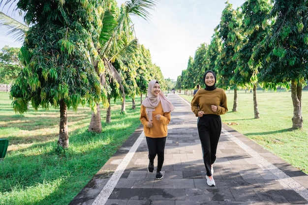 Two happy muslim girls in headscarves do outdoor sports while jogging together in the park