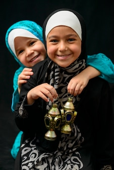 Two happy muslim girls with ramadan lantern on black background