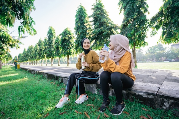 Two happy muslim teenage girls after sports together in the afternoon when breaking the fast and drinking water using bottles in the park
