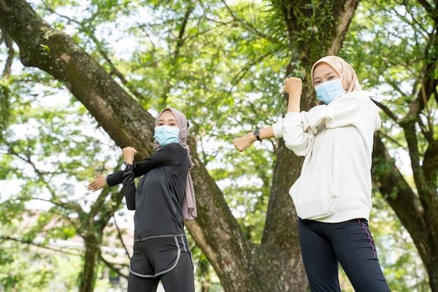 Две счастливые подруги-мусульманки тренируются вместе и носят маску для защиты от вируса covid