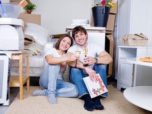 Два счастливых человека сидят на полу в своей новой квартире с бокалом шампанского