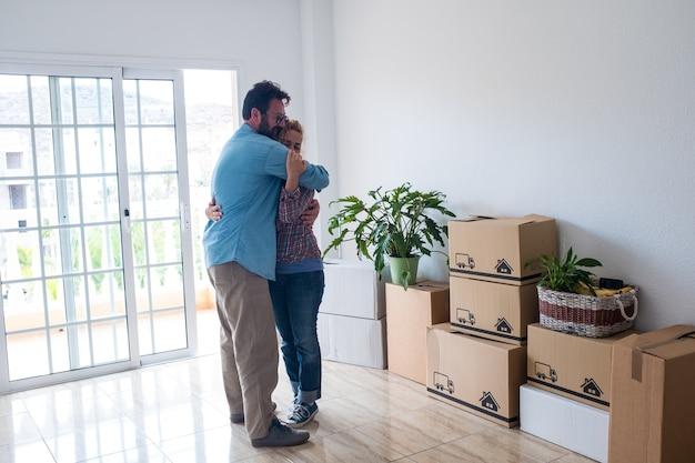 새 집이나 아파트를 구입한 후 포옹을 하는 행복한 두 사람 - 바닥에 상자와 팩을 옮기는 귀여운 커플 - 함께 살고 독립적인 생활 방식을 갖는 귀여운 커플