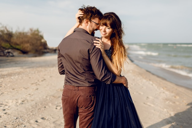 Two happy people in love, elegant woman with her handsome boyfriend hugging and enjoying romantic time together on the beach. elegant dress.