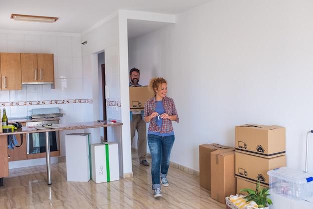 새 집이나 아파트로 걸어가는 행복한 두 사람이 바닥에 상자와 팩을 옮기는 것 - 귀여운 커플이 함께 살고 독립적인 생활 방식을 가지고 있습니다.