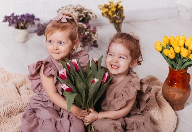2人の幸せなかわいい女の赤ちゃんが座ってチューリップの花束を持っています