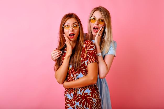 Due belle sorelle felici migliori amici hipster donne divertendosi insieme al fondo rosa dello studio