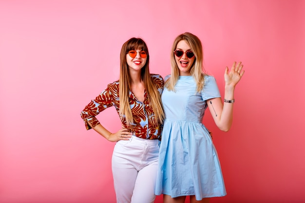 Two happy pretty sisters best friends hipster women having fun together at pink studio background