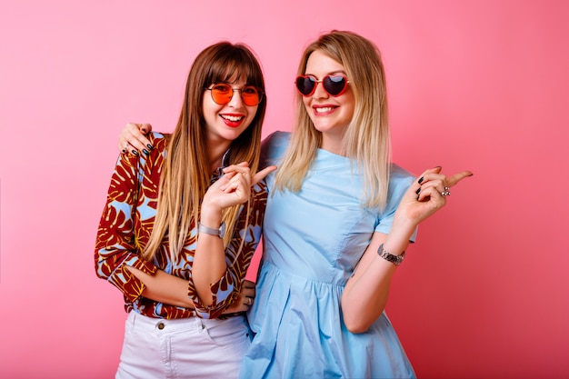 Two happy pretty sisters best friends hipster women having fun together at pink wall, hugs and kisses, happy couple, trendy bright summer clothes and accessories, relationship goals.