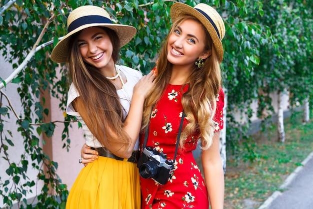 Due sorelle abbastanza giovani felici, abbracci sorridenti ridendo e divertendosi insieme, portando vestiti e cappelli femminili vintage retrò alla moda. all'aperto.