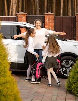 Две счастливые школьницы бегут к матери, встречая их после школы