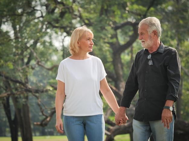 2人の幸せな先輩退職男と女が歩いていると公園で話しています。 Premium写真