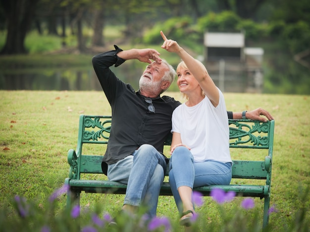 Two happy seniors retirement man and woman are sitting and talking in park