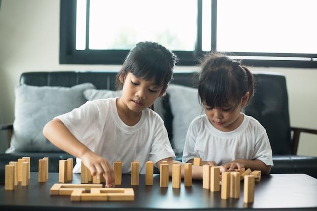 Два счастливых брата и сестры радостно играют в игру с деревянными кубиками дома