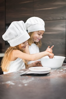 Two happy siblings preparing food in bowl on dirty kitchen counter