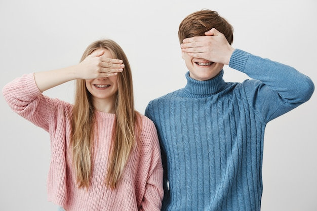 Two happy siblings standing together, guy and girl close eyes with hand