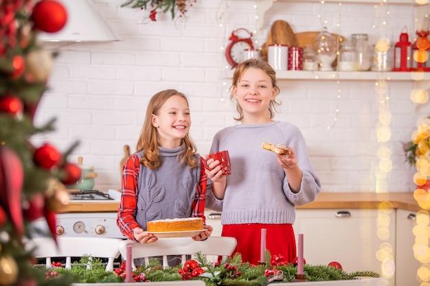 2人の幸せな姉妹が、カップと甘いパイを手に持って、キッチンのクリスマステーブルを飾っています。