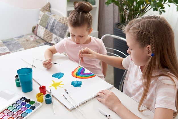 Two happy sisters painting at home, rainbow drawing