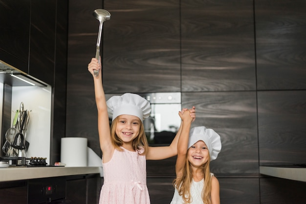 Two happy sisters wearing chef hat in kitchen holding their hands